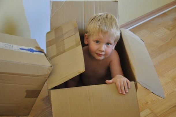 Child sitting in moving boxes - the beginning